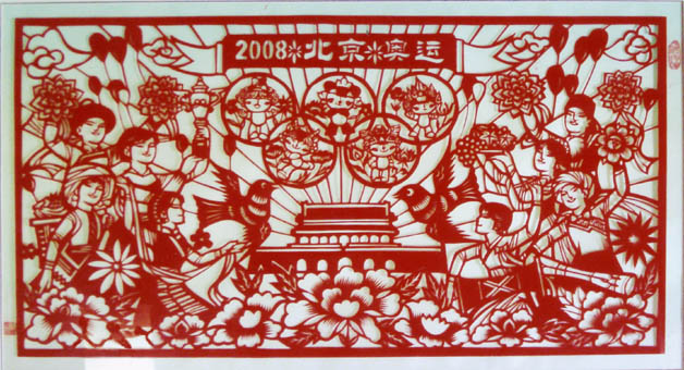剪纸《喜迎2008北京奥运》宽100厘米,高50厘米,作品正中有2008北京奥运字样。中间是奥运标记五环和天安门。五环内剪有五个各具特点的北京奥运会吉祥物福娃,光芒四射的天安门象征着2008奥运会主办地北京,其两侧的是穿着各式民族服装的普通百姓。她们手捧鲜花、水果、奖杯、乐器等物品,载歌载舞地迎接2008年奥运会到来。图案内还有代表奥运给世界带来和平主题的和平鸽、如意祥云以及中国的国花牡丹花。整个作品构思精巧,寓意深刻,场面宏大,气氛热烈祥和,突出了祖国各族人民喜迎奥运的鲜明主题,表